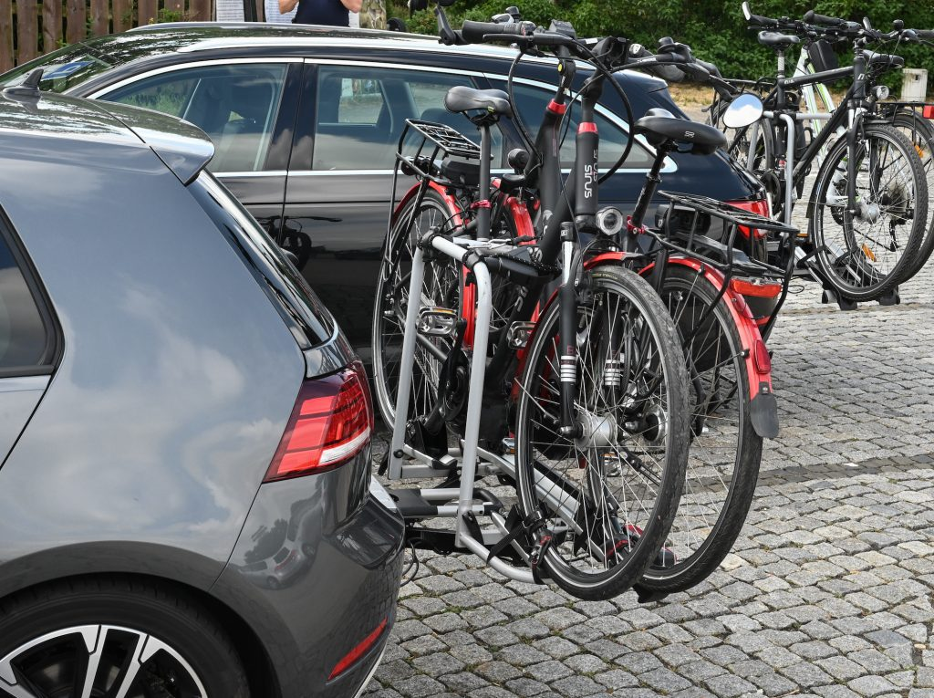 Two vehicles with rear bike racks are parked at a rest area