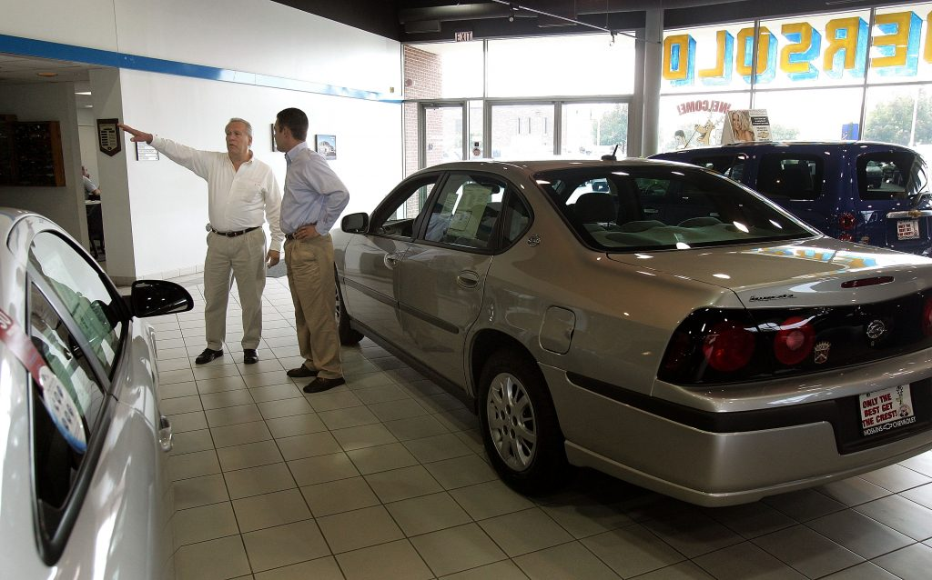 Sales and leasing consultant assists a customer in the new-car showroom