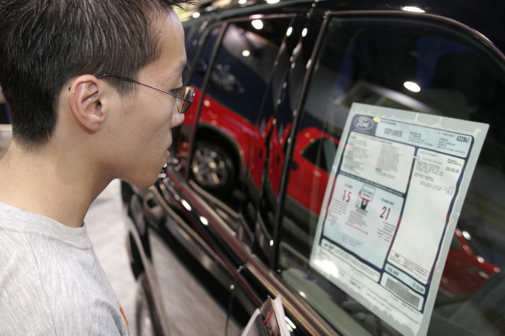 A person looks at a Ford Explorer price sticker, including the MSRP, at the 2005 International Auto Show