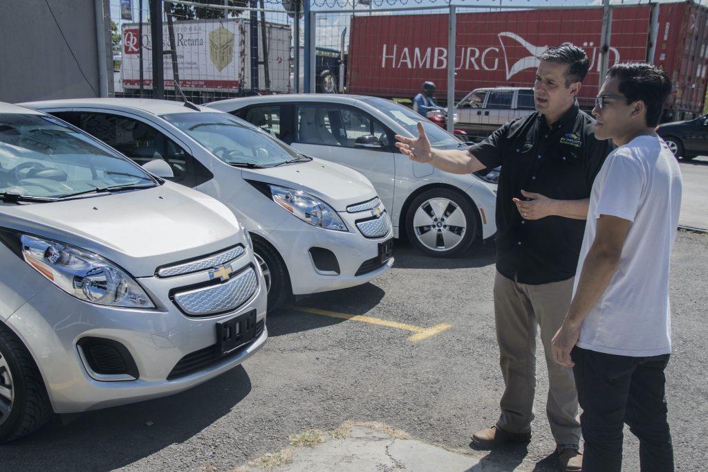 A car dealer talks to a customer on the lot.