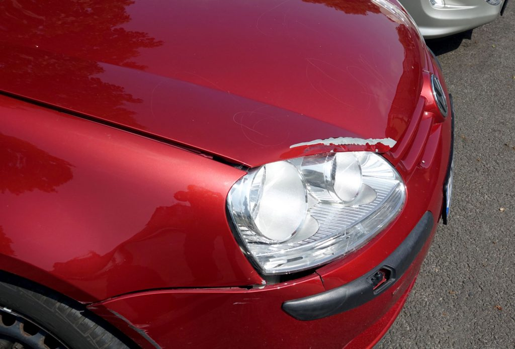 A Volkswagen car with red paint damage above the headlight