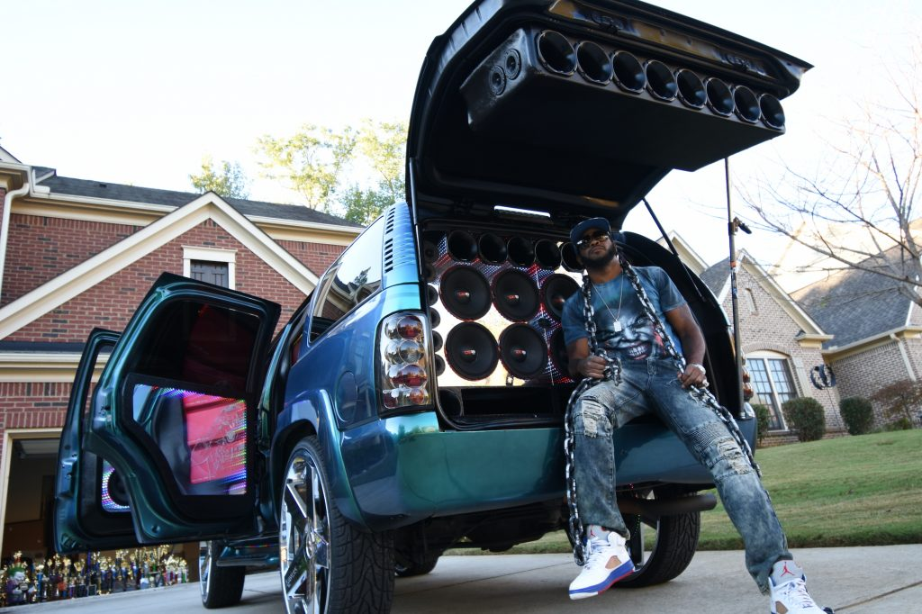 Jay Jones, known as 'Joka' sits in the speaker-filled boot of his customized 2004 Tahoe truck.