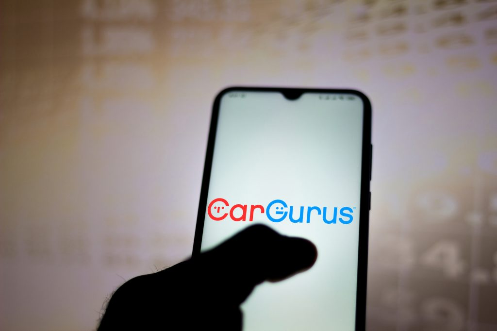 In this photo illustration, the CarGurus logo is displayed on a smartphone.