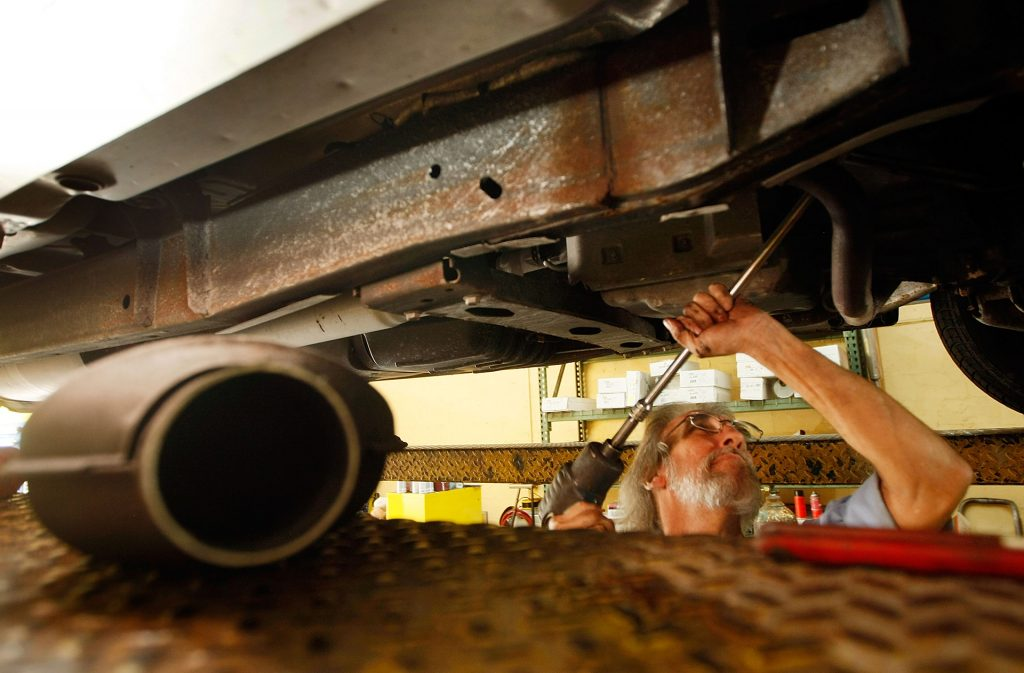 Mechanic installing a catalytic converter.