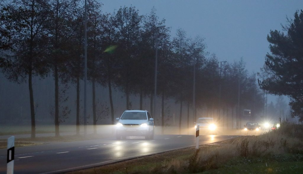 Cars with their headlights on drive on a cloudy morning in November 2018