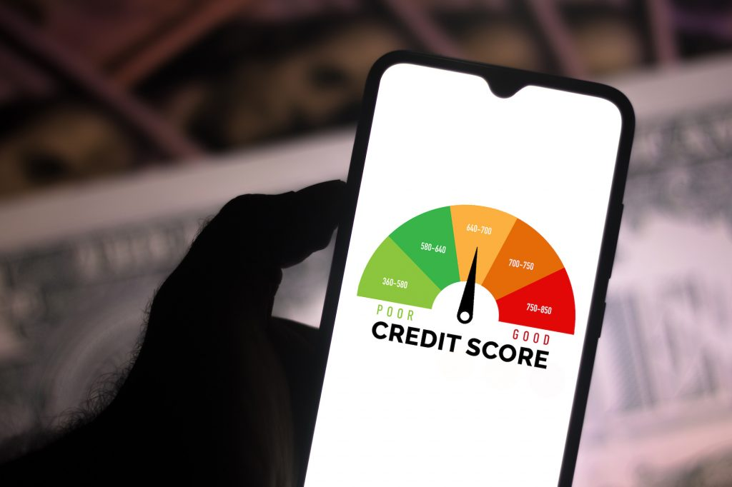 In this photo illustration, a businessman holds his smartphone showing a graph with the credit score.