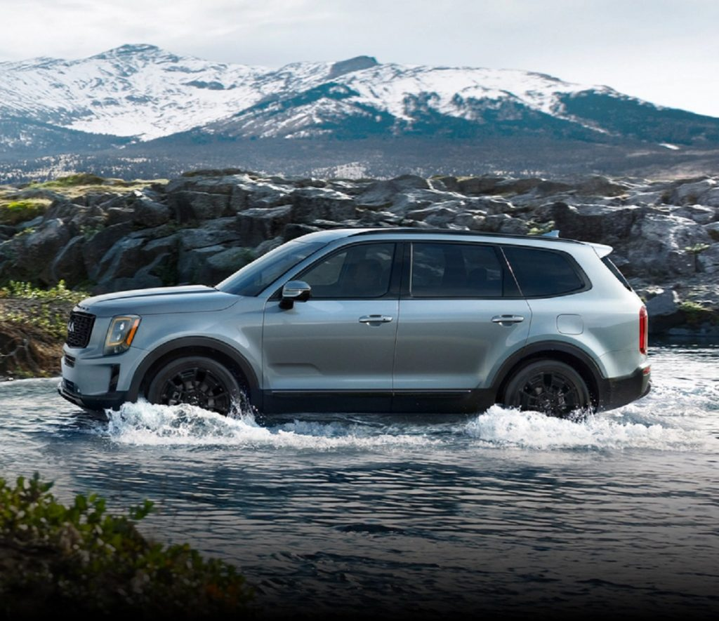A silver 2021 Kia Telluride splashing through a river with a mountain in the background.