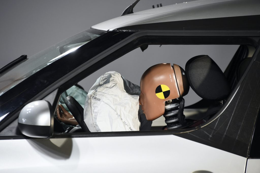 A car and its airbag are pictured after a frontal crash test with another car.