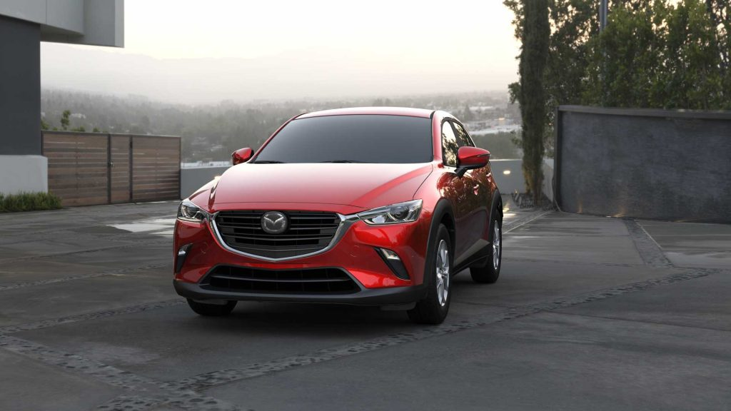 A red 2021 Mazda CX-3 parked with a city in the background.