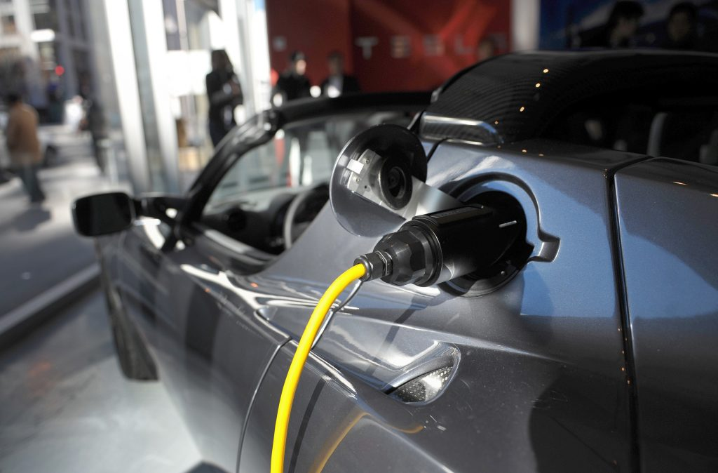original Tesla Roadster plugged in to charge electric batteries