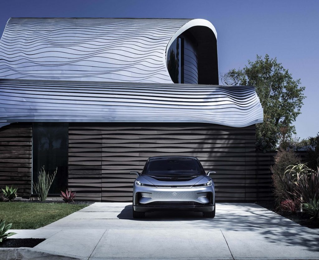 A silver 2021 Faraday FF 91 parked in front of a garage.