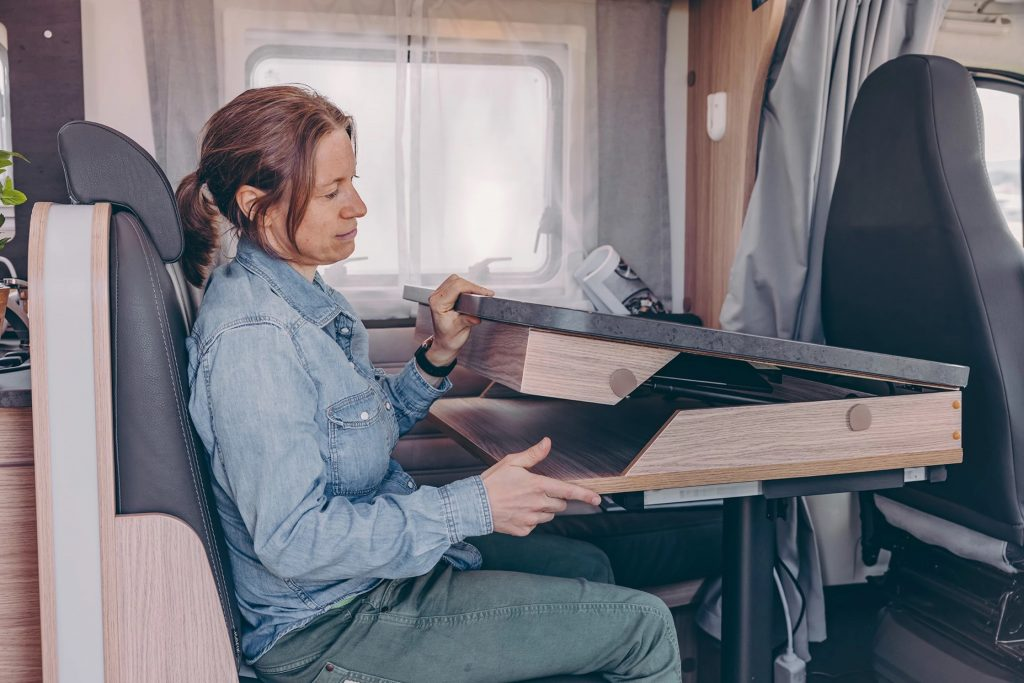 Lady opening up the modular desk that makes the Sunlight Camper the ultimate work remote setup