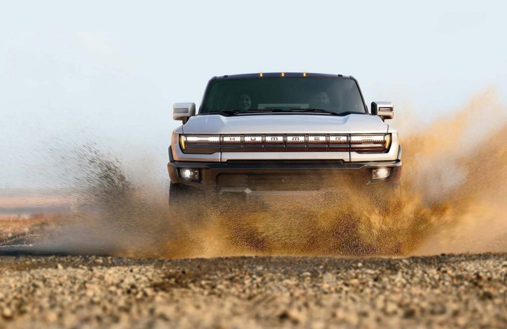 """A publicity photo of a white GMC Hummer EV in the desert captioned """"The GMC HUMMER EV SUV completes the HUMMER EV family and features a 126.7-inch wheelbase for tight proportions and a maneuverable body, providing remarkable on- and off-road capability."""" The Rise of The Supertruck: Brabus, Tesla, and Hummer Lead This New Exotic Truck Class"""