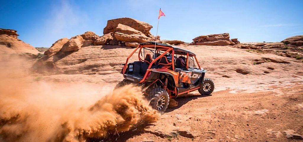 An orange Honda Talon side-by-side UTV model driving fast on a sandy off-road trail