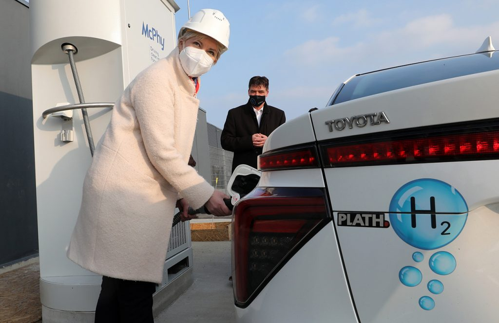 A woman refueling a hydrogen fuel cell vehicle at a hydrogen station.