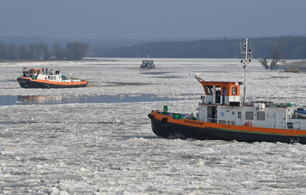 A pair of icebreaker boats sailing in frozen water during winter on the German-Polish border
