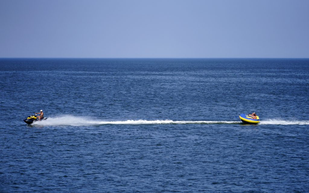 A jet ski tows people riding an inflatable tube in the Baltic Sea in June 2021