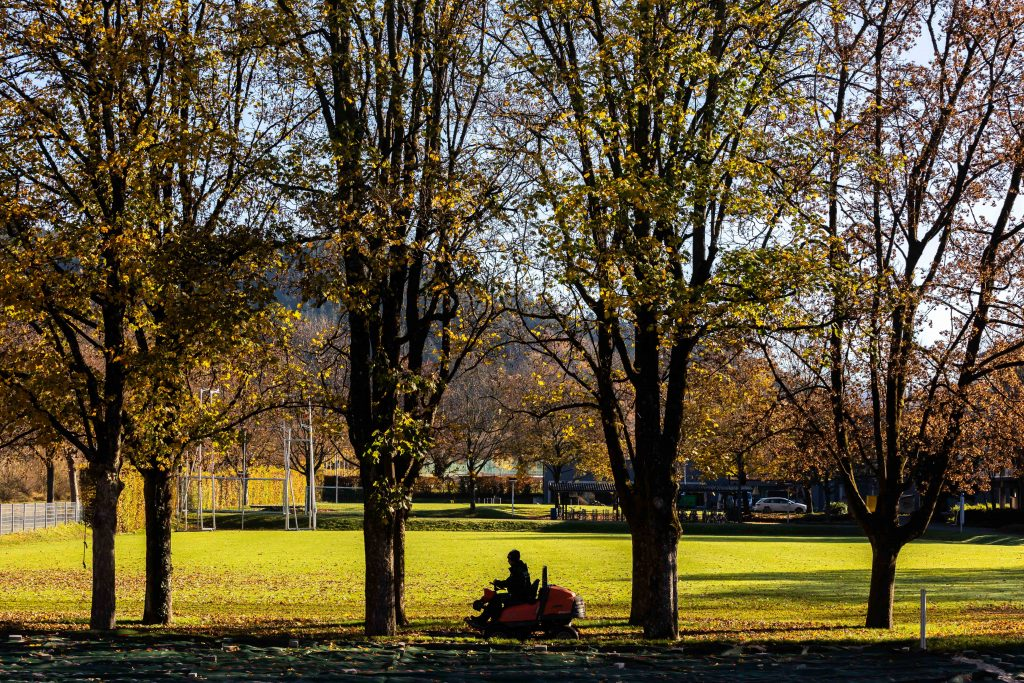 A man mowing the grass on a fall day