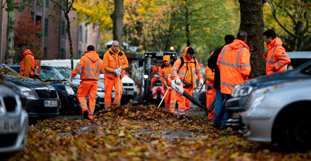 City employees removing leaves in a car parking lot in Hamburg, Germany