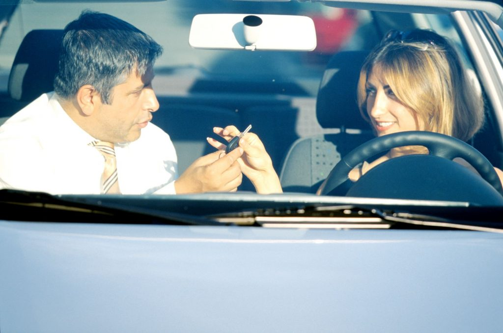A salesman handing over a car key to a young woman driver