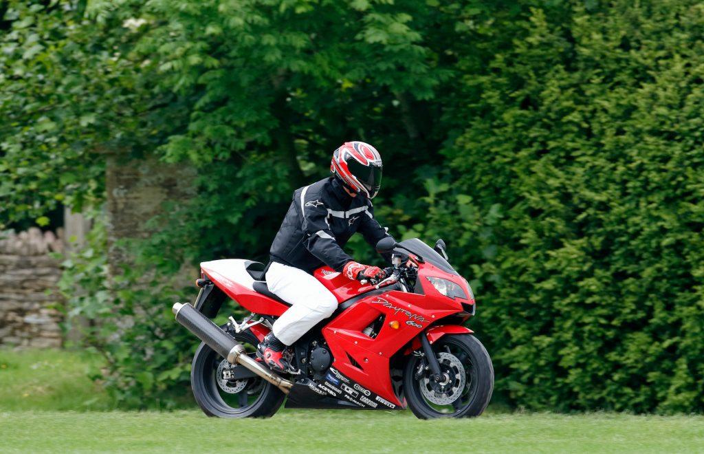 Prince William wears a motorcycle helmet as he rides a Triumph Daytona 600 motorbike in July 2005