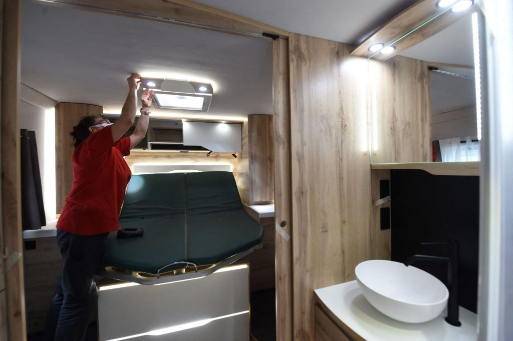 A woman checking the lights in a Le Voyageur motorhome bathroom in France