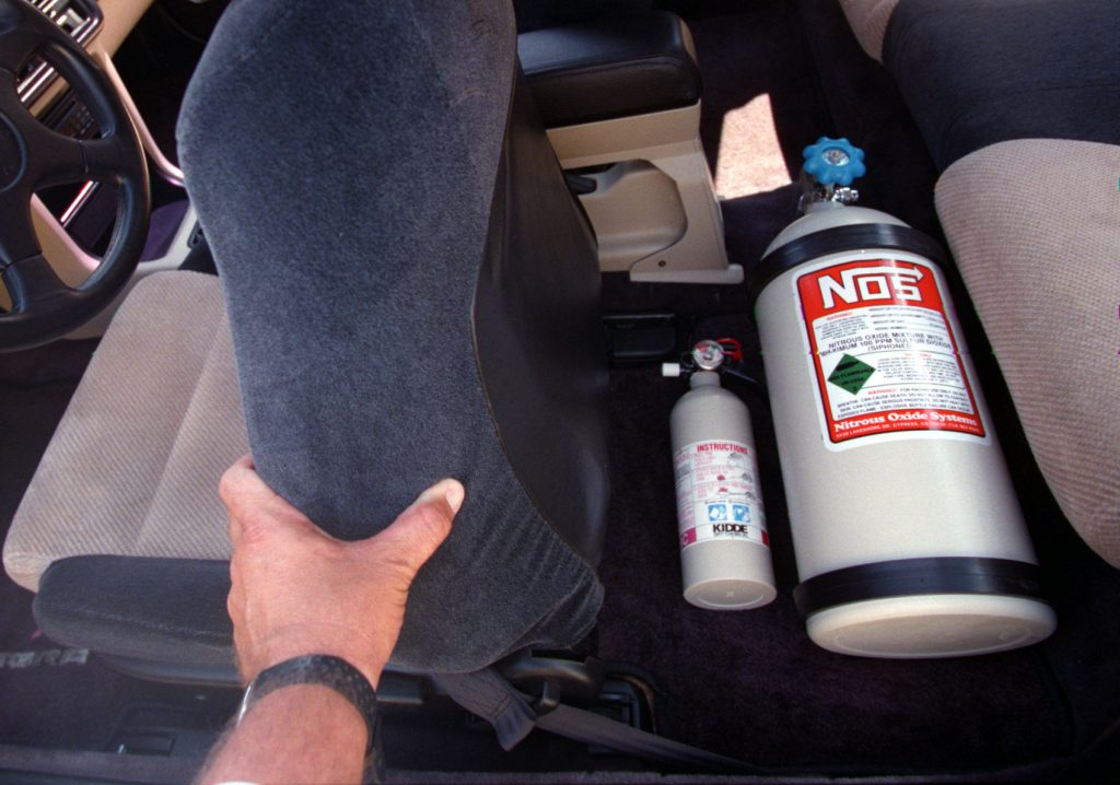 A Nitrous Oxide bottle mounted on the floor in the back seat of this Honda is what gives the car its extra speed under racing conditions