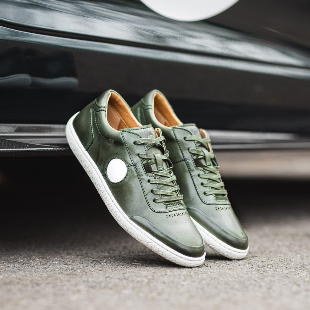 A pair of dark green and white Piloti driving shoes