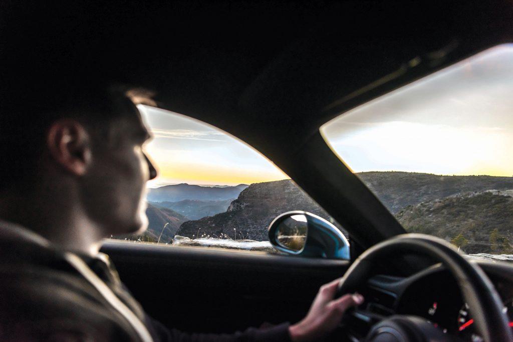 A 2018 Porsche 991 Carrera T sports car driving on the narrow mountain roads of Col de Turini in southeast France.