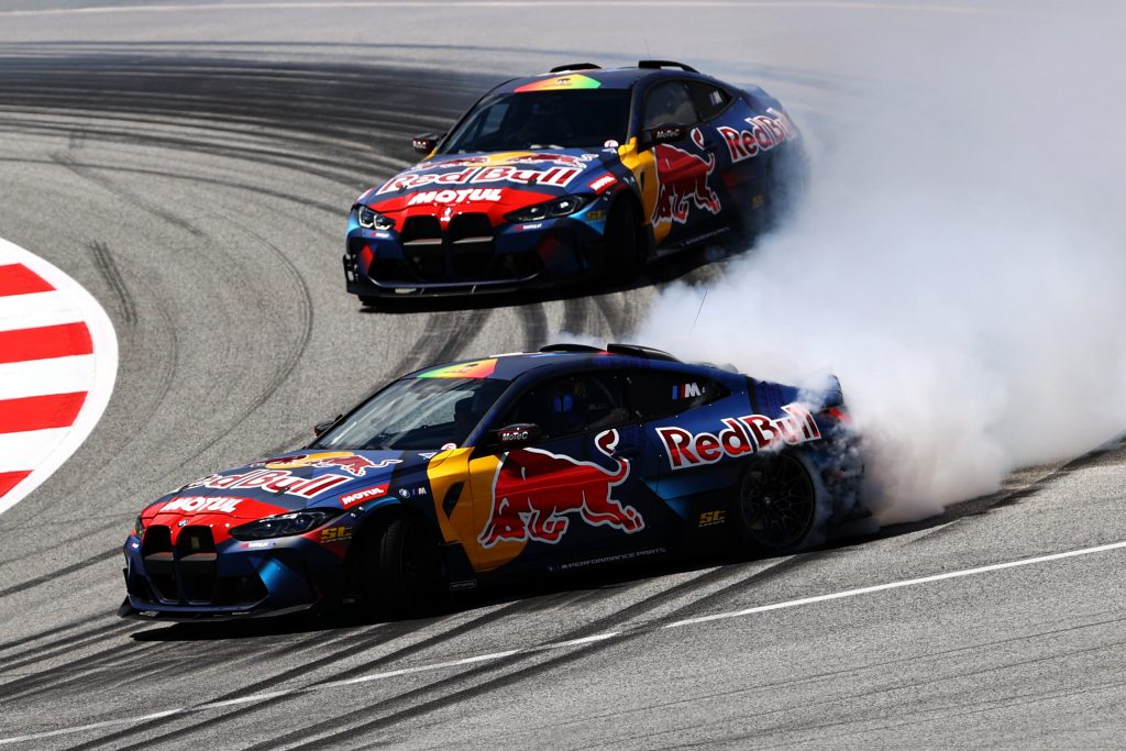 Two Red Bull Cars drifting around a track