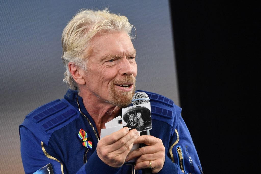 Sir Richard Branson holds up photos that he brought with him into space, as he speaks after flying into space aboard a Virgin Galactic vessel.