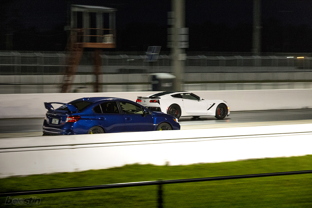 A Subaru and a Corvette Roll Race at a Track