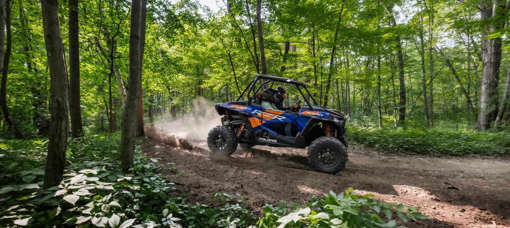 a blue and orange Polaris RZR XP 1000 driving off-road in the forest