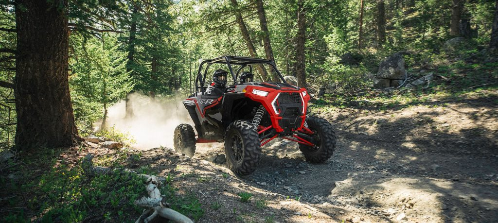 a red Polaris RZR UTV driving off-road in the forest