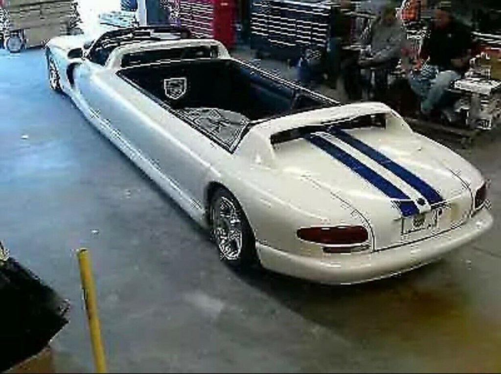 A white 1996 Dodge Viper limousine in a garage.
