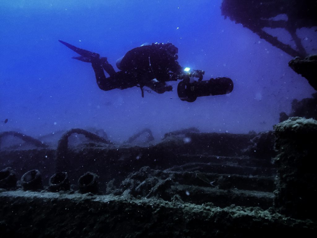A scuba diver uses a sea scooter, also known as a diver propulsion vehicle (DPV), at a shipwreck in August 2017 outside Bonassola Liguria, Italy