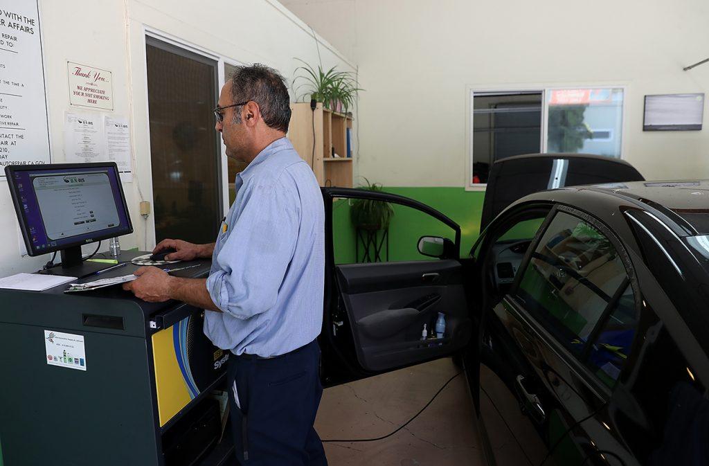 An automotive technician performing a smog check.