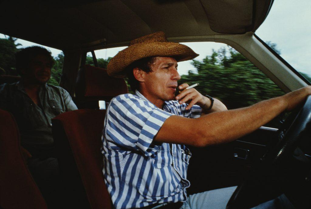 A man smokes a cigarette while driving