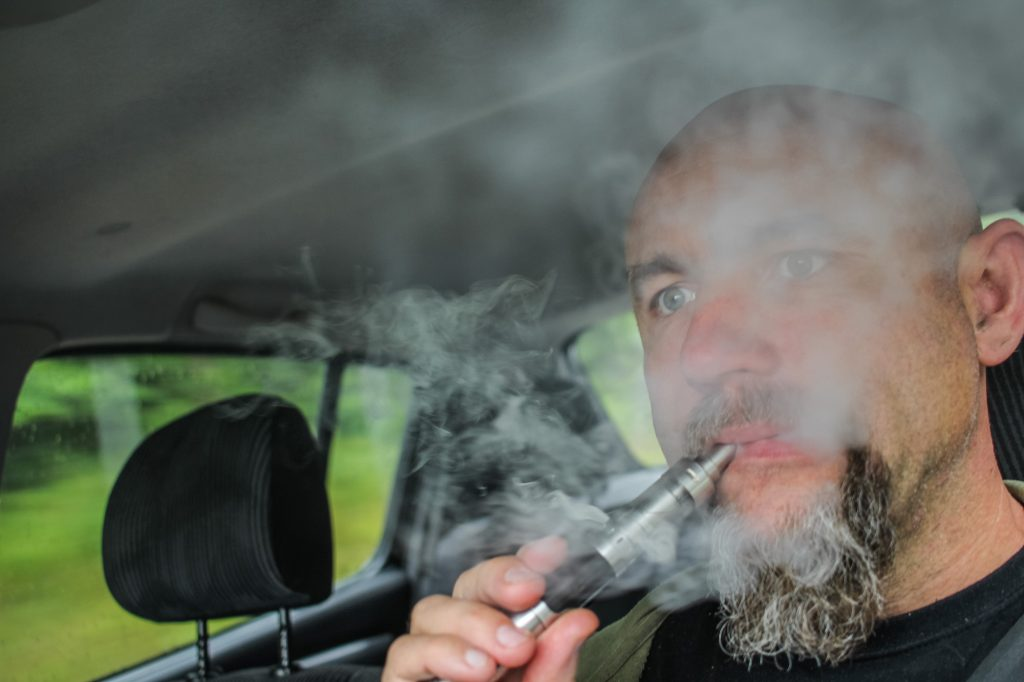 A bearded man vapes while driving a car