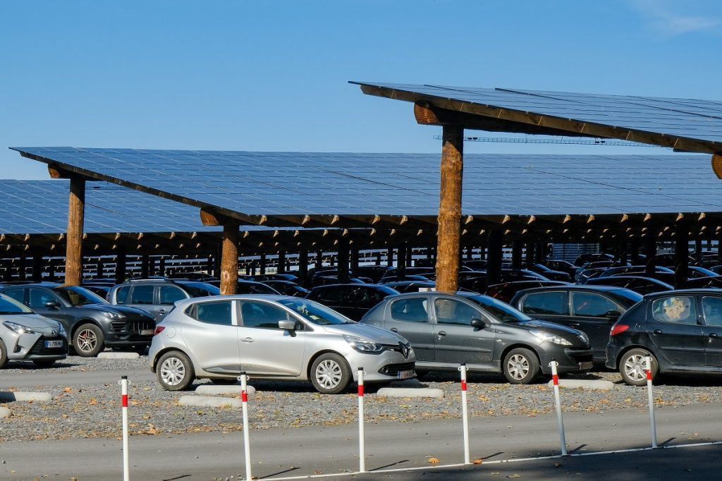 Cars in a parking lot covered by solar panels.