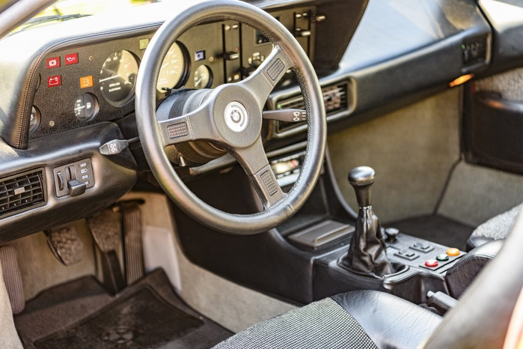 The inside of a car including a stick shift.