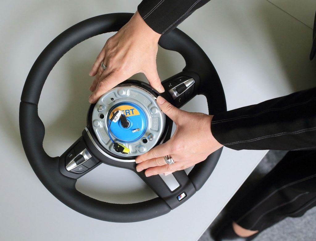 An airbag gets inspected on a steering wheel.