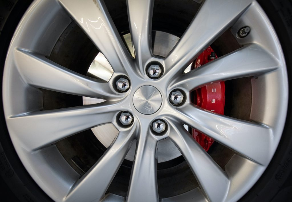 A Tesla logo can be seen on the rim and brake shoe of a Tesla Model X electric vehicle at the new Tesla Service Center.