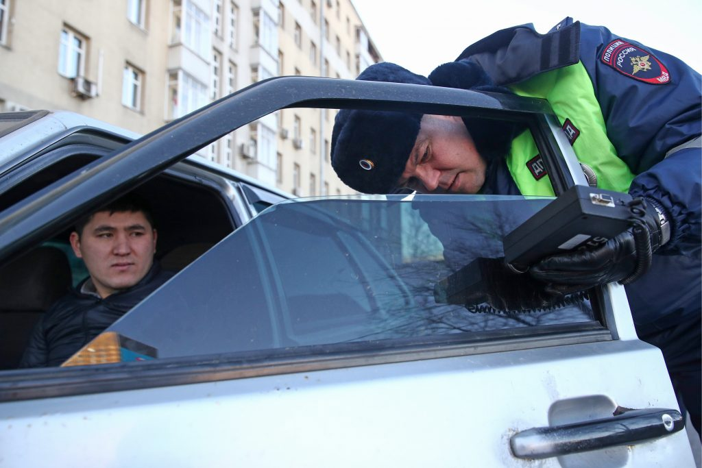 A traffic police officer checking a tinted car window