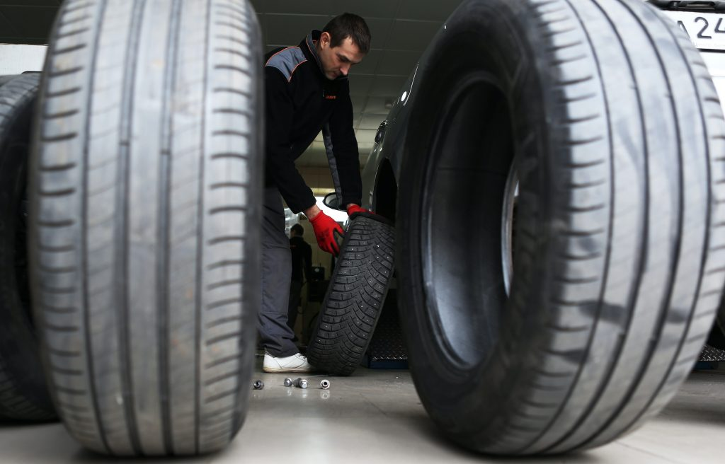 A car service worker fitting winter tires