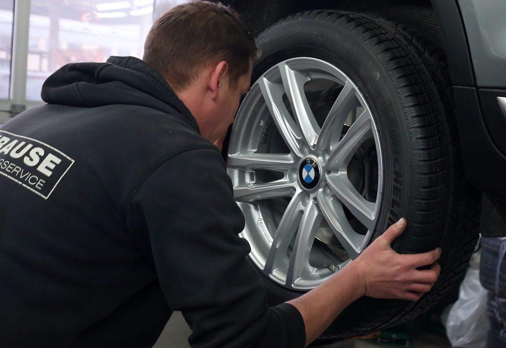A mechanic at a car repair shop rotating tires.