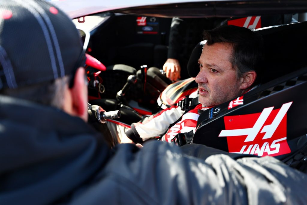 Tony Stewart sits in the driver's seat of a racecar.