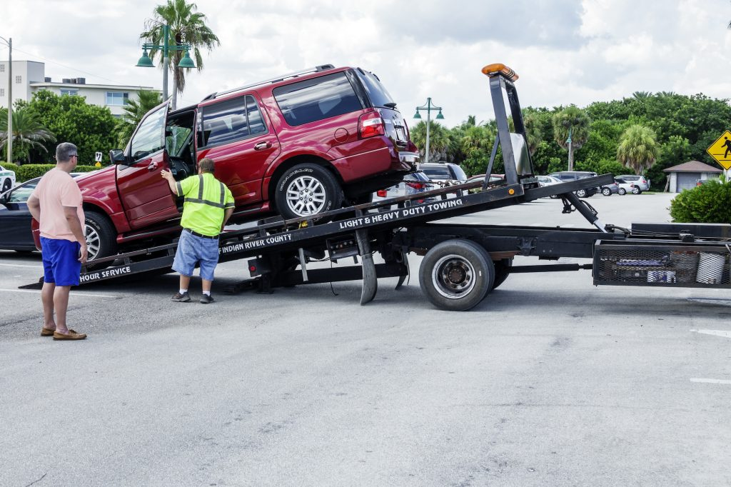 A flatbed tow truck loads a red SUV in a parking lot in Vero Beach, Florida