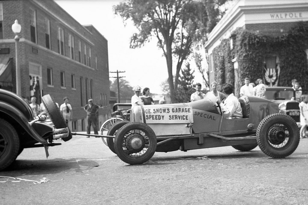 A black-and-white photo of an early racecar being towed by a rope through a town