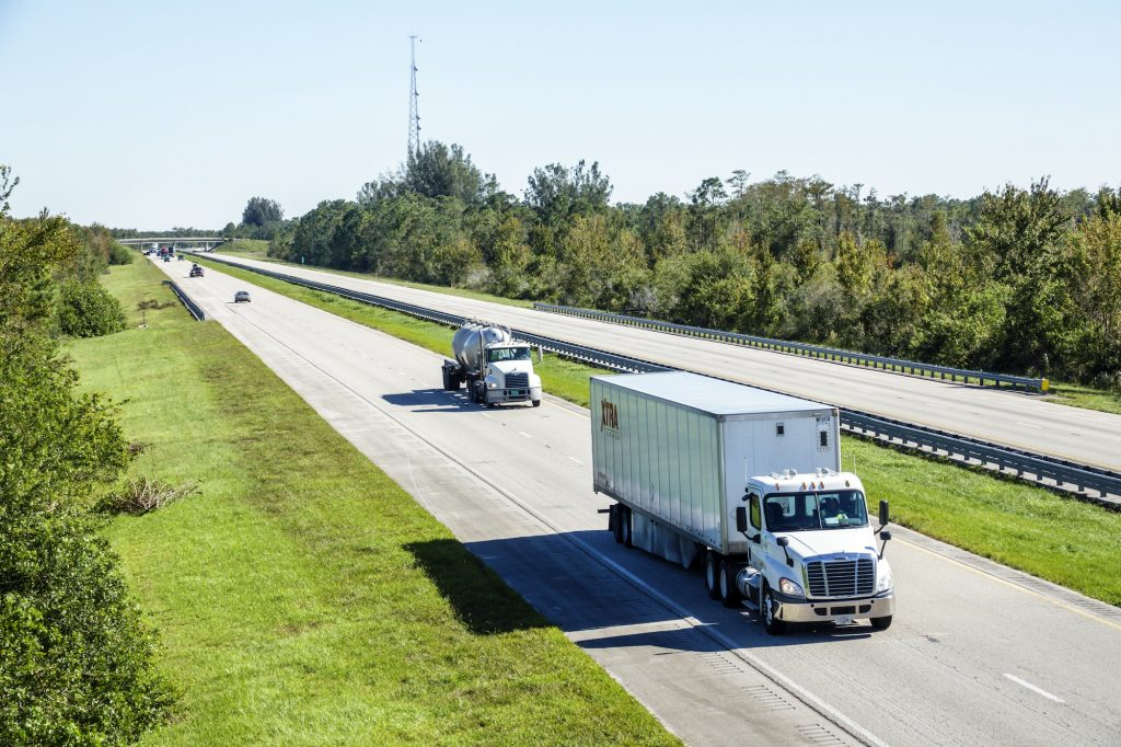 A tractor trailer and a concrete truck on Florida's Turnpike